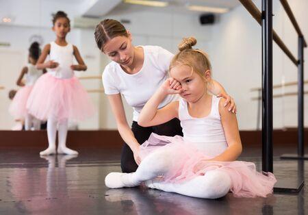 Female ballet teacher supporting little upset girl ballet dancer in choreography hall