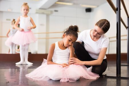 Young female classical dance teacher comforting tired and crying little ballerina in ballet class