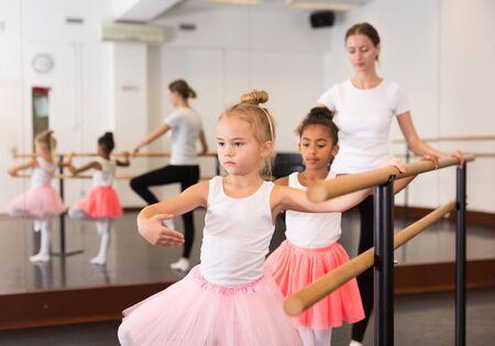 Female ballet trainer teaching two little girls near ballet barre in dancing hall