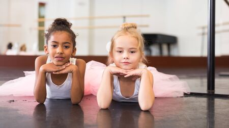 Portrait of two little ballerinas practicing choreography in dance hall