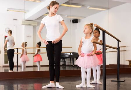 Young female ballet teacher and two little girls in classical dance school 版權商用圖片