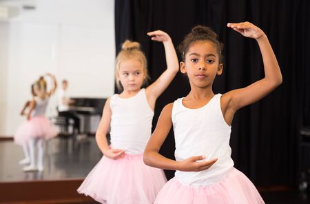 Two little girls practicing ballet elements and positions in dance studio