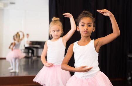 Two little girls practicing ballet elements and positions in dance studio 版權商用圖片