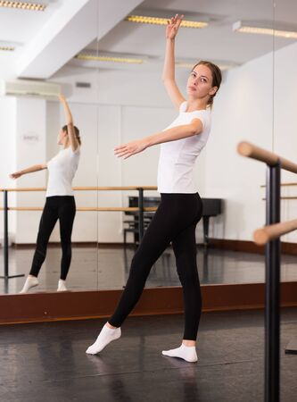 Young attractive woman warming up before training in dance hall