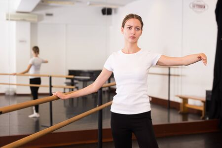 Young female classical dancer training alone in hall classical dance school