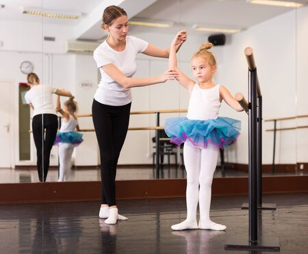 Female classical dance trainer teaching little ballerina in ballet class