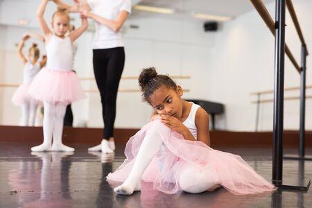 Little upset and tired ballerina sitting on floor during rehearsal in hall of ballet school