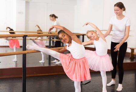 Two little girls practicing choreographic elements on ballet barre with help of teacher in dance school