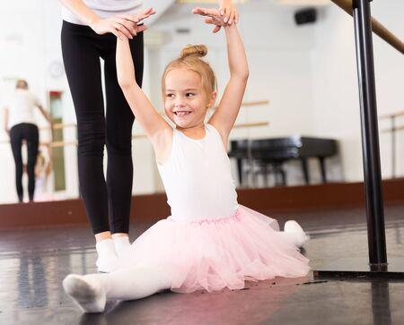 Little ballerina practicing front splits position with help of young female choreographer in dance hall