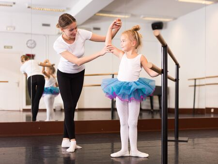 Young female choreographer and little girl in classical dance school