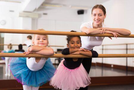 Portrait of two little girls and choreography teacher near ballet barre teacher in dance school 版權商用圖片