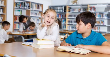 School friends spending time together in library, reading books