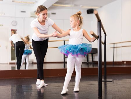 Little ballerina practicing choreographic elements with help of ballet teacher in dance hall
