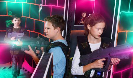 Cheerful happy positive smiling teen girl and boy with laser pistols playing laser tag with friends on dark labyrinth