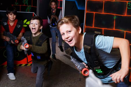 portrait of excited sportive young boy aiming laser gun at other players during lasertag game in dark room