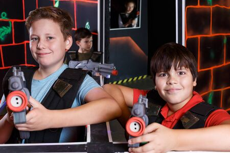 Portrait of two glad teen boys standing with laser guns ready for lasertag game indoors