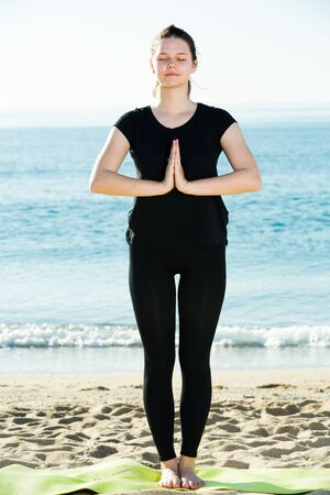 Adult woman in black T-shirt is staying and practicing asana on nature. 스톡 콘텐츠