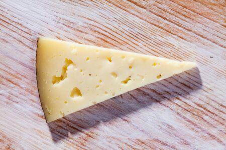 Sliced artisanal semi hard ewes milk cheese on wooden surface