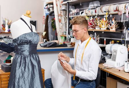 Professional male tailor designing dress style at sewing atelier