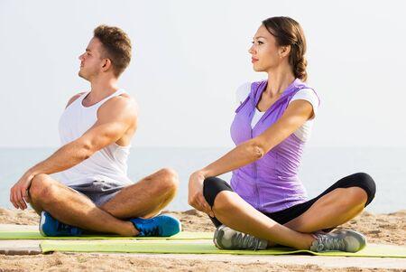 Glad cross-legged guy and girl training yoga poses on seaside
