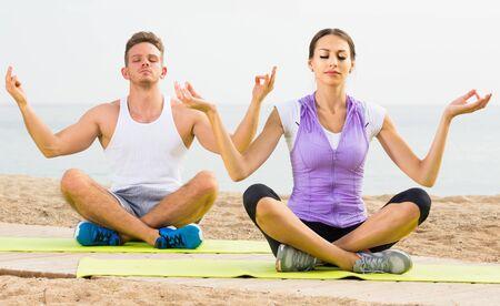 Cross-legged adult spanish couple practice yoga on beach in morning Stok Fotoğraf