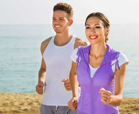 Young glad cheerful positive couple running together on beach by ocean in morning