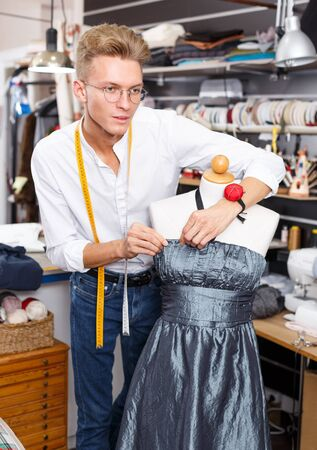Young male dressmaker using tape measure for taking measurements of dummy at sewing atelier