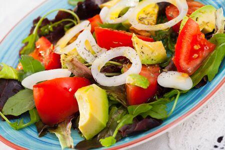 Salad with arugula, green avocado, tomato and  onion at plate