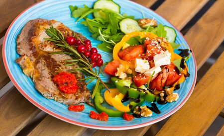 Roasted veal steak with vitamin salad from arugula, cucumber, tomatoes, bell pepper, feta cheese and walnuts on wooden surface