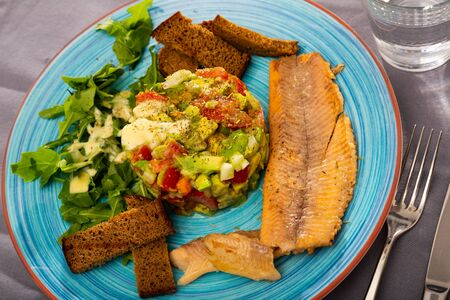 Healthy eating. Vitamin salad from avocado, tomatoes and greens served with grilled fillets of trout and toasted black bread