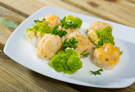 Delicious stewed fish balls with white sauce, steamed broccoli and fresh greens