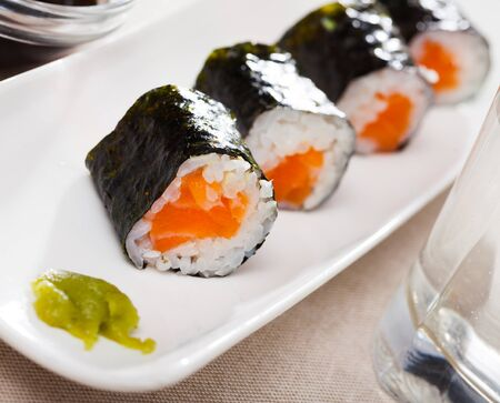 Traditional Japanese cuisine. Sushi maki set with fresh salmon served with soy sauce and wasabi