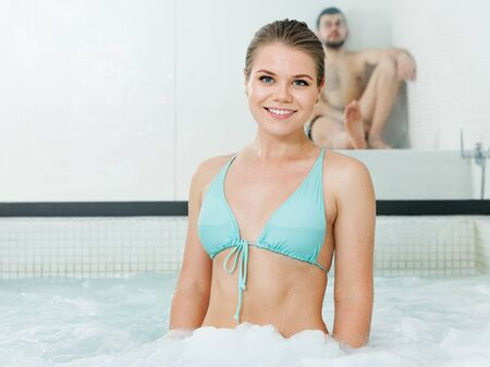 Smiling girl in bikini relaxing in a spa center, posing in a hot tub