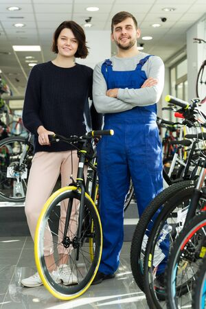 Portrait of young man seller and woman standing in bicycle store