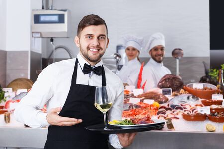 Portrait of man waiter with serving tray offering dishes in fish restaurant