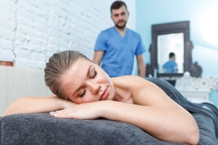 Relaxing professional massage for young woman in spa salon 写真素材