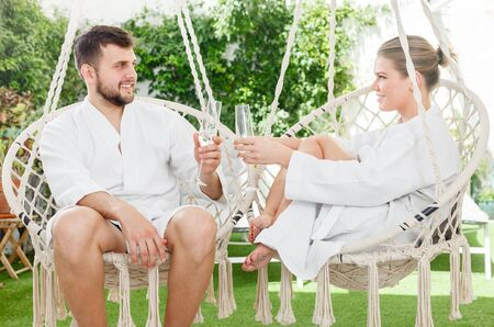 Loving cheerful couple enjoying vacation in the luxury spa resort outdoors. Focus on both persons