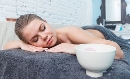 Young attractive woman relaxing after massage in spa center