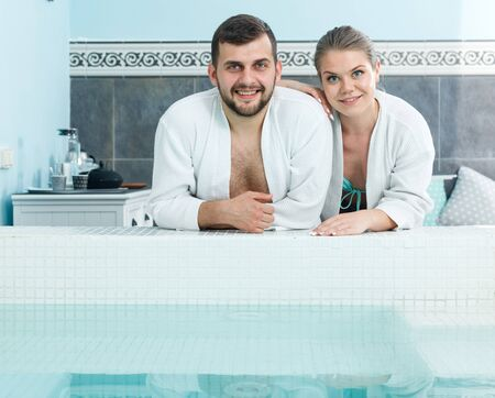 Cheerful young couple in bathrobes standing next to pool in spa center 写真素材