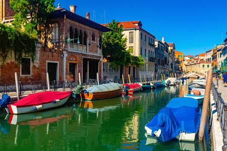 Traditional Venice cityscape with narrow canal, moored boats and ancients colorful buildings on banks of canal, Italy