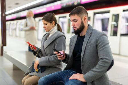 Man with his girlfriend are sitting on the bench with mobile