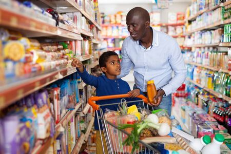 Happy friendly glad  cheerful positive  African family of father and tween son shopping together in supermarket
