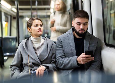 Man en vrouw die telefoon gebruiken binnen tram