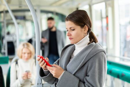 Positive woman reading from mobile phone screen in tram