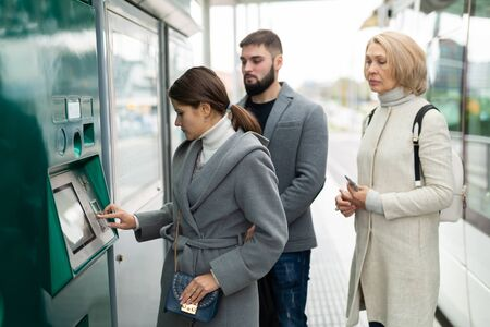 Passengers buying ticket at ticket vending machine