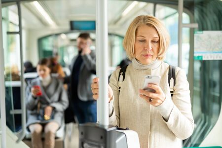 Portrait of focused mature woman absorbed in her smartphone on way to work in modern streetcar in autumn day