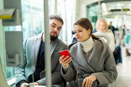 Young couple browsing in their smartphones while traveling by modern city streetcar in autumn day Stock fotó