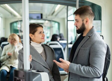 Attractive girl and bearded guy talking in city bus on way to work in fall day Stock fotó