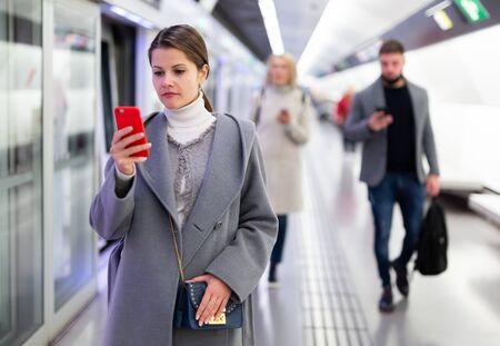 Portrait of female passenger waiting for train on subway platform and reading timetable in phone