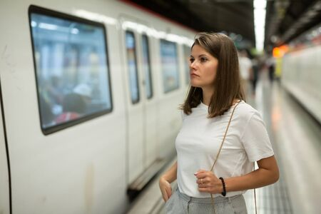 Young woman waiting train in platform of underground station